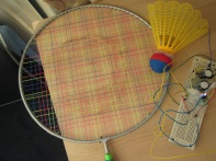 Badminton with coil and magnets producing electricity